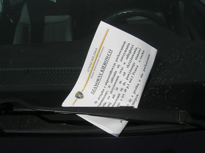 Kartka od straży miejskiej za wycieraczką