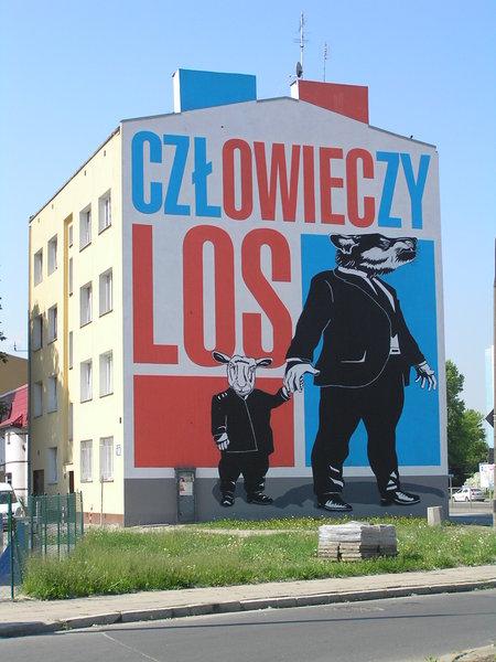 """Mural à Praga, ul. Radzymińska 15O. Jeux de mots sur """"destin humain"""" contenant aussi """"destin de mouton""""."""